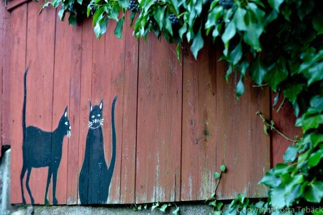 Målade katter på ett plank