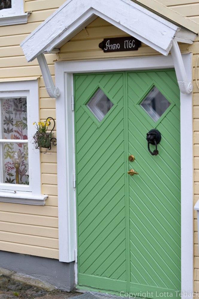 Grön dörr till litet hus